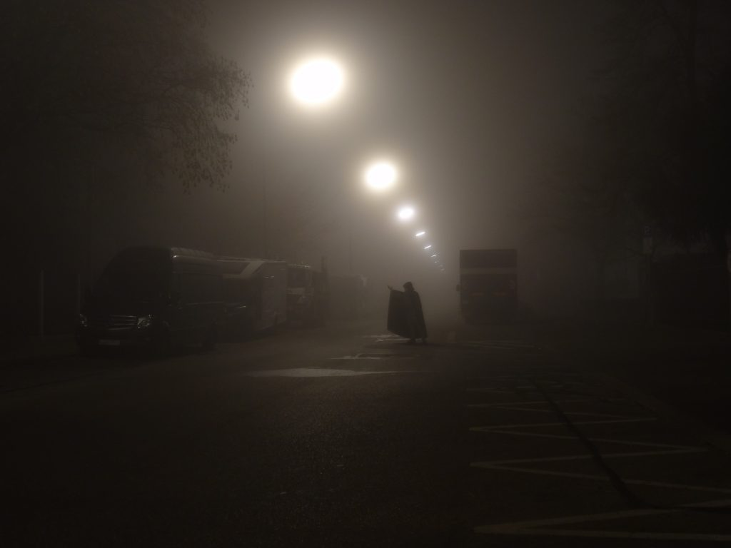 This photograph shows a narrow two-lane city street during foggy weather conditions. Due to the fog, the many street lamps appear as soft, floating sources of very unfocused light. In the middle of the street, the silhouette of a man wearing a black cape and dark grey pants can be seen. The man has turned away from looking at the camera and is looking to the right. He has raised his right hand as if he was trying to catch the passing fog.