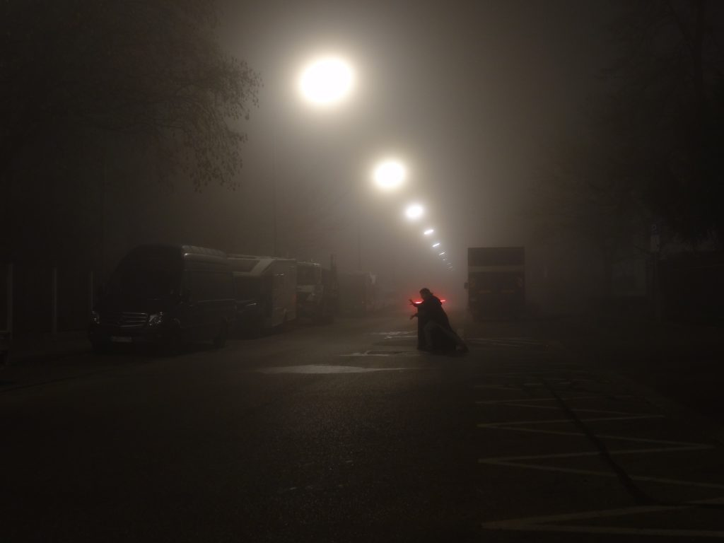 This photograph shows a narrow two-lane city street during foggy weather conditions. Due to the fog, the many street lamps appear as soft, floating sources of very unfocused light. In the middle of the street, the silhouette of a man wearing a black cape and dark grey pants can be seen. The man has turned away from looking at the camera and is looking to the right. He has raised both hands in a punching motion to the right and his fingers are mimicking the claws of a tiger. Behind the man, a red glow may be perceived. This stems from a car's rear lights that were accidentally recorded by the camera's long exposure.