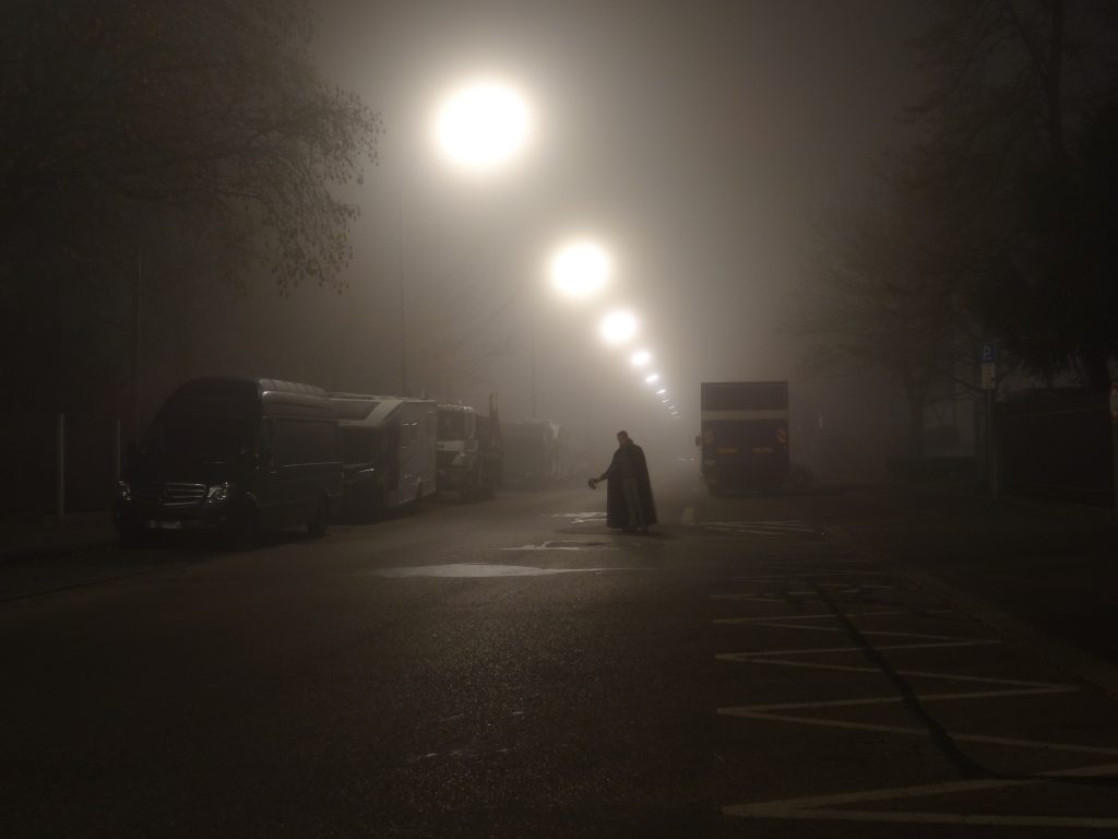 This photograph shows a narrow two-lane city street during foggy weather conditions. Due to the fog, the many street lamps appear as soft, floating sources of very unfocused light. In the middle of the street, the silhouette of a man wearing a black cape and dark grey pants can be seen. The man has turned away from looking at the camera and is looking to the right. He is facing the camera and is holding a face mask in his right hand. It seems as if the man has just taken off the mask and unveiled his identity.